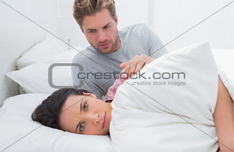 Sad woman ignoring her partner in her bed