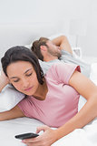 Woman using her phone while her partner is sleeping