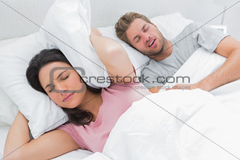 Woman covering her ears with pillow while her husband is snoring