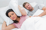 Woman covering ears with pillow while her husband is snoring