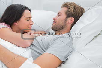 Attractive couple awaking and looking at each other