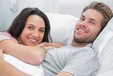 Happy couple awaking and looking at camera