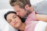Man kissing his sleeping wife on the cheek