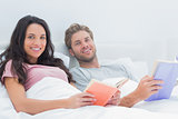 Cheerful couple holding books