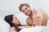 Man giving thumb up next to his sleeping wife