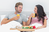 Attractive couple having breakfast in bed