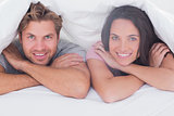 Couple smiling under the duvet