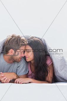 Beautiful couple head against head under the duvet