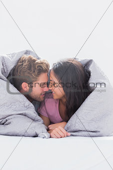 Beautiful couple wrapped in the duvet