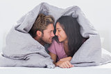 Attractive couple wrapped in the duvet