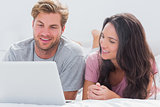 Couple using laptop in bed