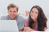 Cheerful couple using laptop in bed