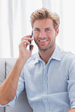 Man smiling while he is having a phone conversation