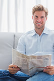 Cheerful man reading a newspaper on a couch