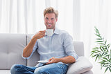 Man sitting on his couch drinking a coffee