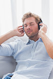 Man relaxing while listening to music on a couch