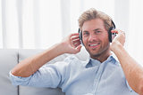 Man listening to music with headphones in the living room