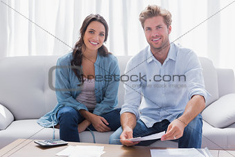 Couple doing their accounts sat in a couch