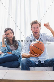 Woman looking at her husband cheering the basketball game