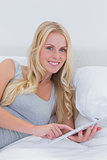Woman touching her tablet in bed