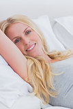 Cheerful woman relaxing on her bed
