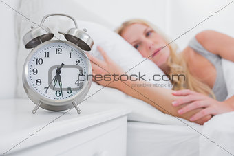 Tired woman looking at the alarm clock