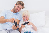 Cheerful father and son playing video games