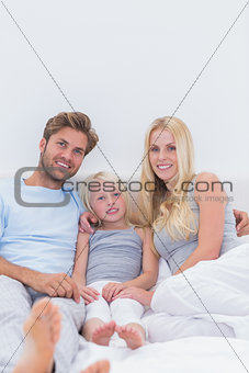 Beautiful family sitting in the bed