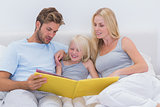 Couple reading a story to daughter
