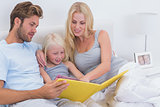 Beautiful couple reading a story to daughter