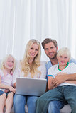 Portrait of a cheerful family using a laptop