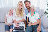 Cheerful family using laptop in the living room