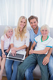 Smiling family using laptop in their living room
