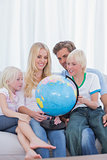 Happy family looking at globe on couch