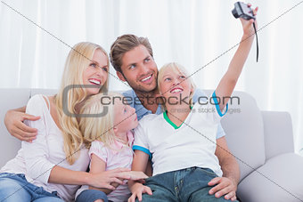 Little boy taking pictures of his family