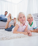 Cute children lying on the carpet smiling at camera