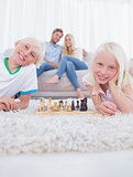 Children lying on carpet playing chess
