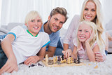 Smiling family playing chess together