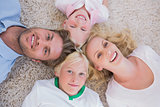 Overhead of family lying on the carpet
