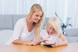 Mother using digital tablet with her daughter