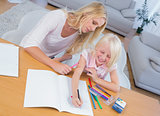 Mother and daughter drawing together at table