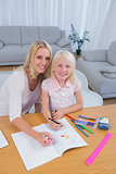 Smiling mother drawing with her little girl