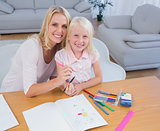 Mother and daughter drawing together and looking at camera