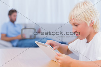 Boy using tablet pc while his father is reading