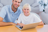 Smiling father and his son using laptop