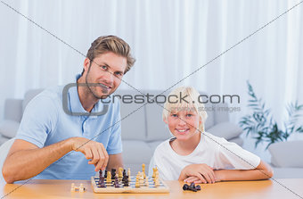 Little boy playing chess with his father