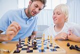 Father and his son playing chess together