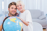 Father and his son looking at globe and smiling
