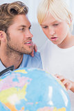 Father looking at globe with his son