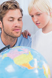 Father and son looking at globe together